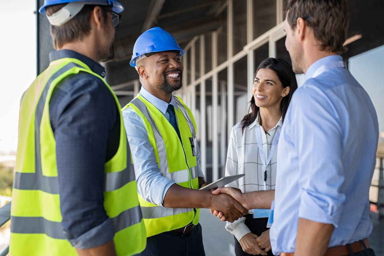 Construction-team-shaking-hands-outside-building-the-samuels-group